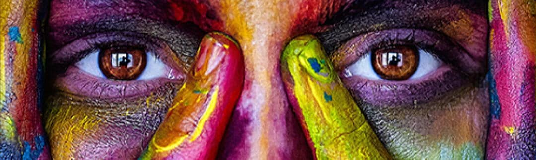 close up photo of a woman's eyes and painted face