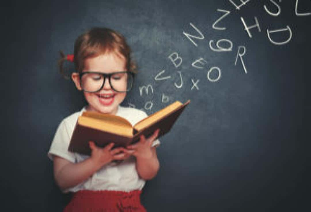 Young girl with glasses reading a red book.